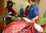 Doug Reeves, 13, cq, squeezes bags of wrapped presents through a doorway while volunteering for...