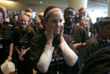 Hyatt Regency employee Lisa Griswold, who works on the culinary team, covers her ears to avoid the...