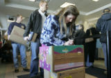 Susan Scialo (cq) from Highlands Ranch, writes addresses on her packages as she waits in line at...
