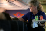 Southwest Airlines flight attendant Sandra Bogan, cq, serves beverages to passengers on a flight...