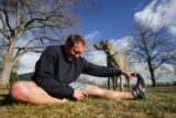 Ian Dawe (cq), strecthes before going on a run with his dog Murphy at Washington Park in Denver ,...