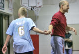 Chris Johnson (cq), 16, left, (will add info about their disorders) gets a hand shake from coach...