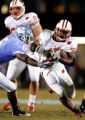 Wisconsin's Brian Calhoun evades UNC safety Carey Mahlon on the drive that ended with his first...