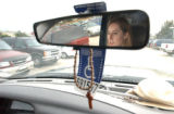 (Denver,CO,Shot On 4/8/04-- A wooden cross and a handicap plaque hang on the rear view mirror of...