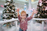Dylan Keener, 3, cq, plays with artificial snow in the Narnia display at the Cherry Creek Shopping...