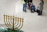 Graham DeClue, 1, left, and his brother Grant, 3, nap in their stroller near a Menorah (Hanukkia -...