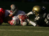 Nebraska Cornhusker wide reciever Terrence Nunn,left, is pulled down by his face mask by Colorado...