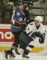 Colorado Avalanche player Ian Laperriere, left, gets tripped up by Vancouver Canuck player Nolan...