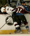 Vancouver Canucks player Nolan Baumgartner,left, is checked by Colorado Avalanche player Cody...