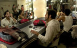 Mathenee Stefan Treco(cq), front, puts on makeup while other cast members of the musical Aida...