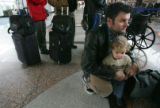 Mark Lyon (cq), holds onto his son Quincy Lyon (c1), right, while waiting in line at Midwest...