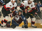 Colorado Avalanche center Joe Sakic, middle, gets caught between  l Ottawa Senators' Brian...