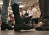 Abdul Qayum Abdulrashid (CQ), middle, tries on his government issue combat boots as he  joined 20...