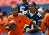 Jaisean Jackson (cq, left), 9, of Denver runs with the football during a drill at the Kids Caravan...