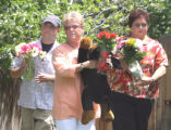 L to R: Family friends Rick Anderson (cq), Lynn Fowler (cq), and Mary Dameron (cq) carry flowers...