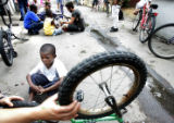 Adgn Noor,6, gets a helping hand with a bicycle repair Thursday afternoon in an alleyway behind a...