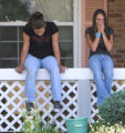 L toR: Miranda Millard (cq),14, and Taylor Ross (cq),11, sit across the street from  yesterday's...
