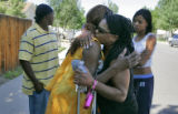 Felecia Ford (cq) in yellow, the mother of Michael Ford, is hugged by a family member, in black, ...
