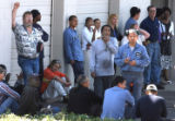 Evacuated workers wait outside  during a magnesium fire at Timminco Corp. at 3595 Moline Street in...