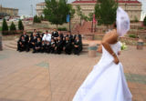 Bride Sharlie Tafoya's (cq) veil blows in the wind as her husband Joseph, cq, center, in white,...
