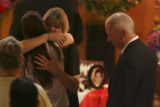 Elaine Meyer, mother, center, blonde hair facing camera, gives an emotional hug to an unknown...