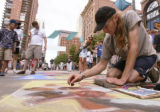KAS060 James Tinker (cq) works on a sidewalk art piece during the annual La Piazza dell'Arte chalk...