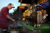 Ruben Martinez, cq, left, cooks barbeque ribs while talking to his mother-in-law, Delphine...