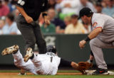Jamey Carroll, of the Rockies, is tagged out by Mark Sweeney in a pick-off play in the second...