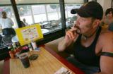 Mike Papousek, of Idaho Springs, smokes before getting his lunch at Pete's Kitchen in Denver,...