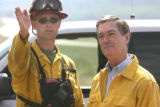 Forest Information Officer Steve Segin (cq) and Gov. Bill Owens watch ground crew members fighting...