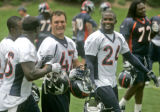 Denver Broncos' John Lynch, left, and Champ Bailey, right, are all smiles as they walk off the...