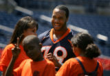 Denver Broncos fullback Kyle Johnson (#39) laughs with a few of the children attending Thursday's...