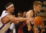 Kings Brad Miller stretches for the ball around Jazz Andrei Kirilenko at Arco Arena Sunday. The...