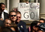 04/19/2004 Denver-A protestor holds a sign behind  hundreds of Denver cops who rallied on the...