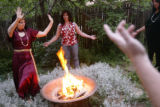 KAS059 Magdalena Merovingia (cq), left, dances around a fire while Ann Axelrod (cq), center, and...