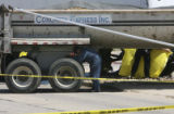 "Investigators inspect the truck, foreground, as police put up a ""media sheet"" around the..."