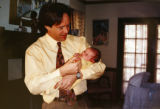 KAS023 John Accola holds his newborn son, Jacob, in a picture taken at his old house about 13...