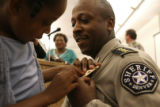 Gary Wilson, has his Division Chief badge pinned on by his daughter Courtney Wilson, 6, during a...