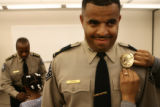 Elias Diggins, foreground, has his badge of Major pinned on his uniform by his wife Francesca...