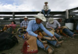 Dusty Seeley (cq), 23, center, prepares his saddle with a group of cowboys before the saddle bronc...
