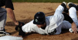 Colorado Springs Sky Sox Jeff Baker dives back into firstbase ahead of the pickoff attempt in home...