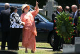 Paulette Paugh Davis, left, and Pam Paugh, center, hold hands at the end of services for their...