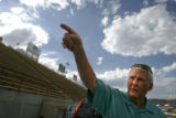 John C. Bandimere Jr., 68, CQ, points at the Chuck Silva memorial on top of the stands at the...