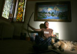 Gary Michael, CQ, 69, sits with his dog Uriah under his painting of Mt. Sneffels which he climbed...