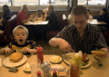 **1/26/06** Patrick, 5, and his father Jeff Webb (both are from Fort Collins) eat hamburgers for...