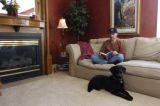 Jay Massey (cq) reads a book while his dog Torie rests at his feet Wednesday morning January 25,...