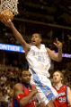 (DENVER, Colo., Jan. 27, 2005) Marcus Camby goes up for the basket over (lt-rt) Cuttion Mobley,...