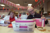(LT. to RT.) Volunteers Erna Mentzer and husband Neil Mentzer, both 88 sort through valentine...