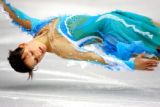 Ukranian figure skater Tatiana Volosozhar is twirled in a circle just inches off the ice by her...
