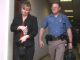 Jeanne Norman (cq), wife of Kelvin Norman, is escorted back into court by Colorado State Trooper...